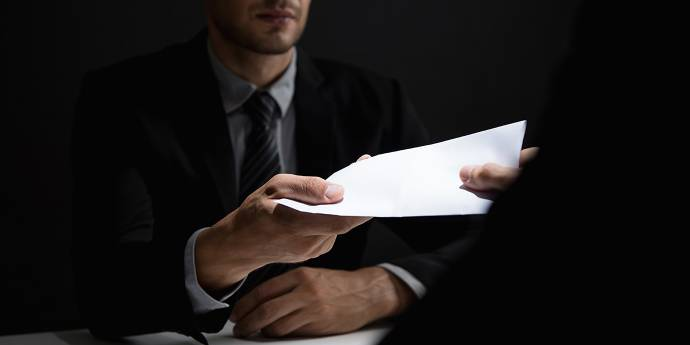 Man handing over a document to another person
