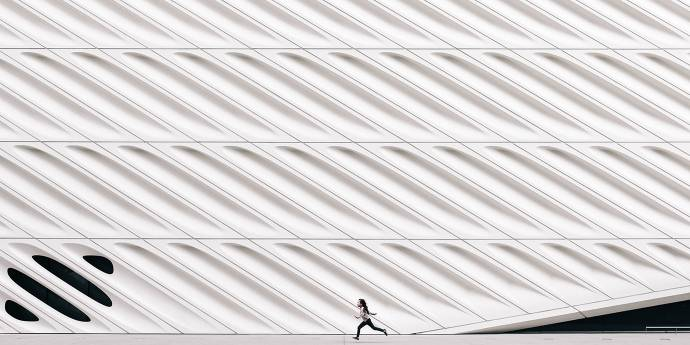 Person running along road next to white modern building