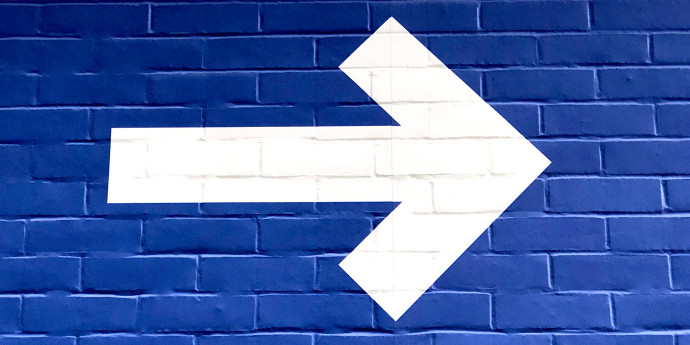 white arrow painted on blue brick wall
