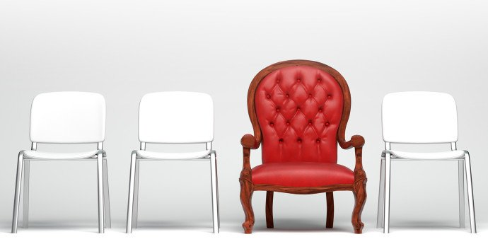 three white chairs and on red chair lined up in a row